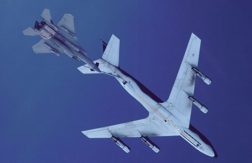 An F-15 approaches a KC-135 flying tanker to refuel.