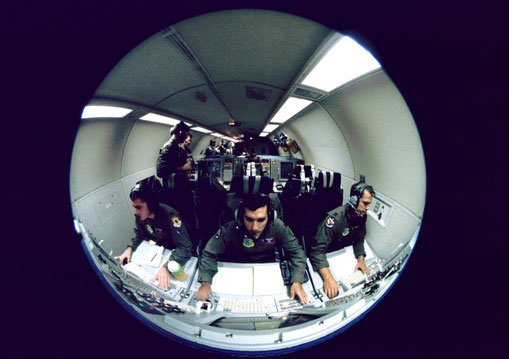 Inside an E-3 AWACS aircraft, radar controllers monitor fighters in an aerial battle.