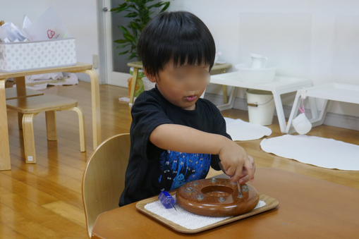3歳児がモンテッソーリ活動のネジ回しのお仕事に集中して取り組んでいます。
