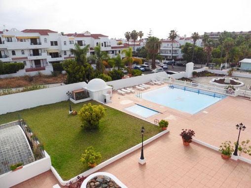 Vom Balkon der Wohnung schaut man auf den Gemeinschaftspool und die Grünanlage von der Wohnanlage.