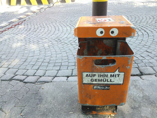 Mülleimer, Auf ihn mit Gemüll, orange, gepflasterte Straße