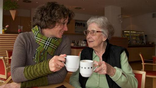 Senioren-Assistenten mit Seniorin beim Kaffeetrinken