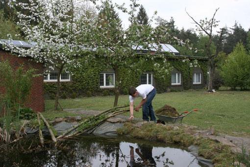 Ein Praktikant bei Ausbesserungsarbeiten am Tümpel. Die Obstbäume stehen in voller Blüte. Im Herbst findet das traditionelle Mostefest mit den im Obstgarten geernteten Früchten statt.