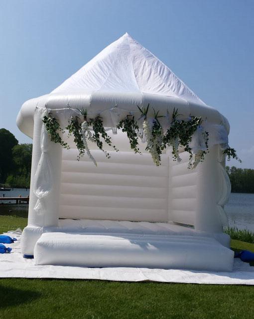 die weiße Wedding-Hüpfburg in 4x4 m mit Tüllstoff und Blumenschmuck