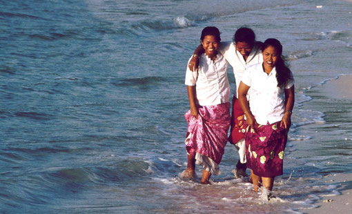 NIcobarese girls take an evening stroll on an island beach, Andaman and Nicobar Islands, India.