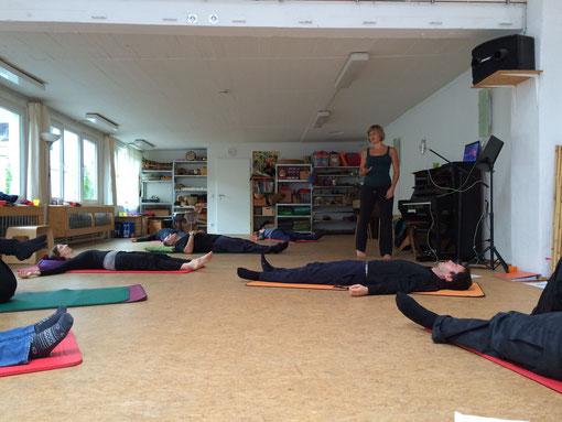 Bild von einer Übung zur Wahrnehmung. Die Teilnehmer liegen auf Matten auf dem Boden.