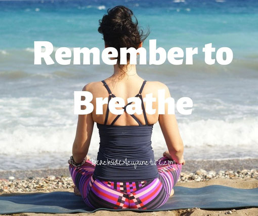 """Remember to breathe"" over woman sitting cross-legged on the beach"