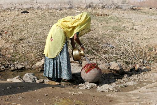 Frau holt Wasser