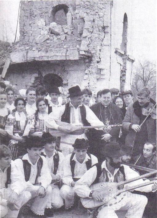 Kardinal Puljić s članovima folklornih skupina iz Posavine, uz ruševine crkve u Dubici, 1996. godine