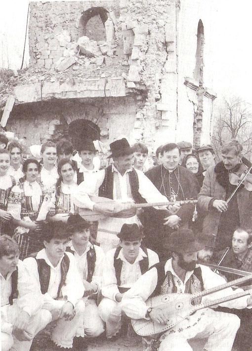 Kardinal Puljić s članovoma folklornih skupina iz Posavine, uz ruševine crkve u Gornjoj Dubici