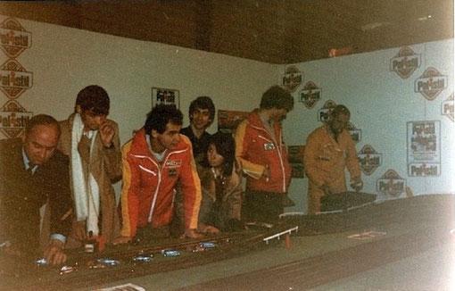 Salon de Bordeaux 1979 le journaliste d'AutoHebdo Eric Bhat avec l'écharpe blanche et les pilotes motul Bertrand Balas et Philippe Streiff autour de la piste de slot racing