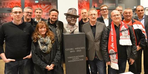 Die Georg-Melches-Initiative und Unterstützer vor der Büste im Foyer des Stadions