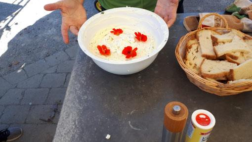 Bild des Ergebnisses der kleinen Kräuterwanderung des Kinderferienprogramms: Eine Schüssel voller Kräuterquark, dekoriert mit Blüten.