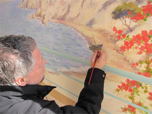 Tony donne le dernier coup de pinceau en plaçant une petite barque sur la plage de la fresque.