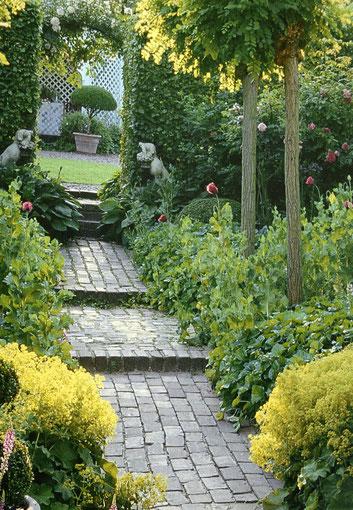 Gartenweg mit kleinen Pflastersteinen und Staudenbeeten