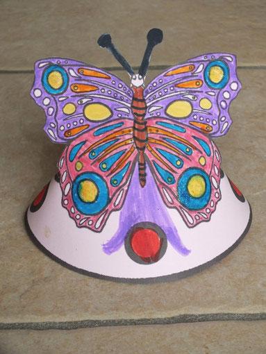 """papillon en coloriage feutre et paillettes avec demi-cercle en dessous, découpage et agrafé à l'arrière, pour former un """"cône"""" à pauser : coloriage en """"3d"""""""