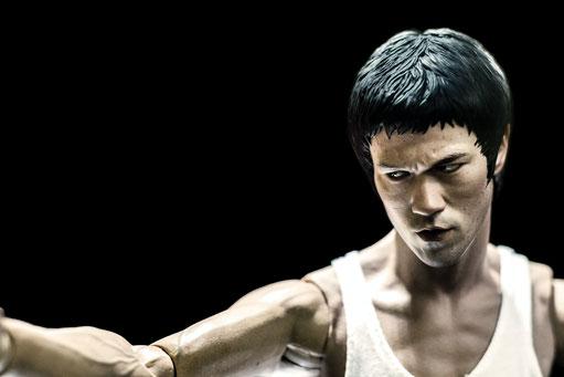 Auf dem Bild ist eine Action-Figur von Bruce Lee zu sehen. Das Bild ist in Schwarz-Weiß.
