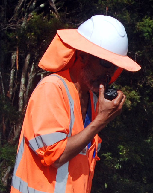 Road works traffic controller with sun-hard hat on the Wellsford to Pakiri road.