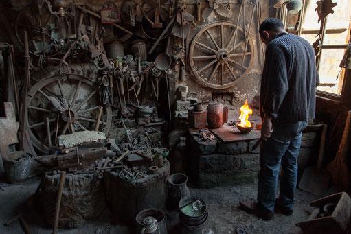 Der Kupferschmied arbeitet in seiner überfüllten Werkstatt an einer Lampe