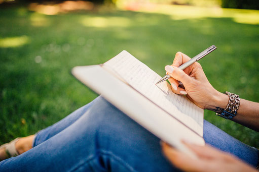 Frau sitzt im Gras und macht sich Notizen