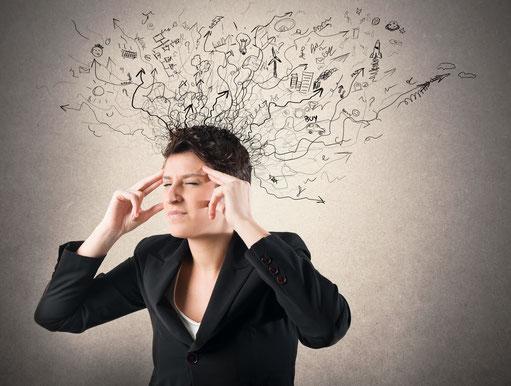 Eine gestresste Frau greift sich mit den Händen an den Kopf