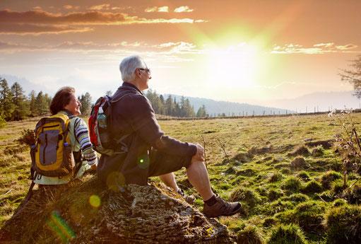 Älteres Ehepaar in Wanderkleidung sitzen auf einem Stein und schauen in den Sonnenuntergang