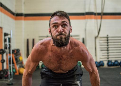 Mann trainiert im Fitnessstudio und hat keinen Spaß