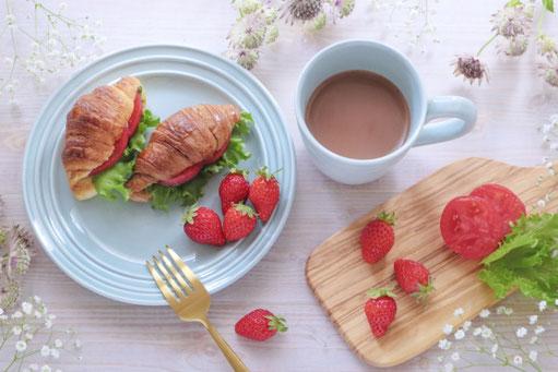 遅めのブランチ。お皿に盛りつけられたクロワッサンのサンドイッチといちご。ミルクコーヒーの入ったマグカップ。カットボードのうえのトマトといちご。