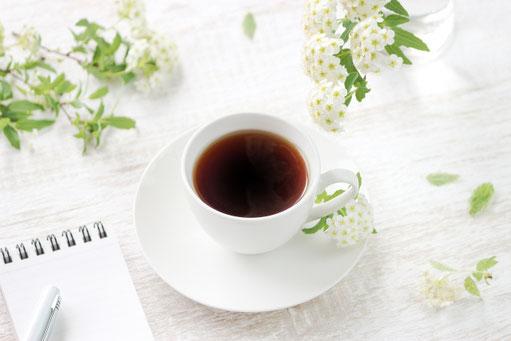 テーブルに置かれたコーヒーの入ったカップ&ソーサ。傍らにメモ帳とボールペン。ガラスの小瓶に活けられたコデマリの花。