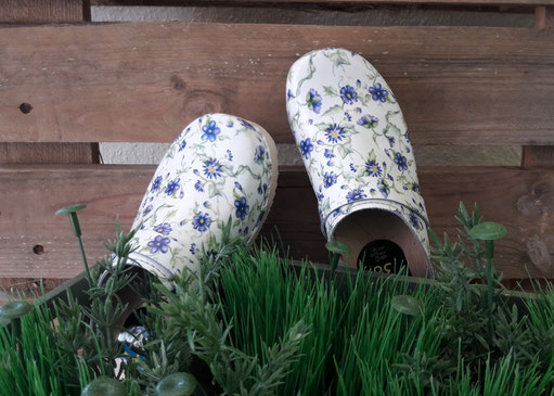 Weiße Clogs aus Holz mit blauen Blumen