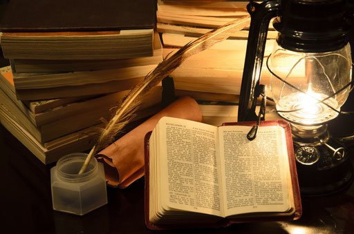 Bücherstapel, Tintenfass mit Feder, offene Bibel und Laterne mit Kerze