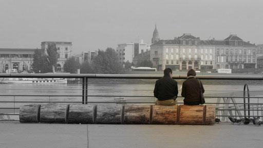 Couple assis sur une bille de bois, en bordure des quais bordelais
