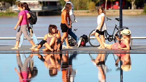 Duo de jeunes femmes en train de se faire pendre en photo par une troisième complice, miroir d'eau, Bordeaux