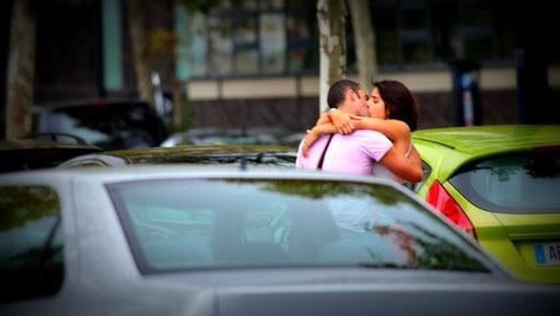 Couple d'amants s'embrassant fougueusement entre des voitures stationnées
