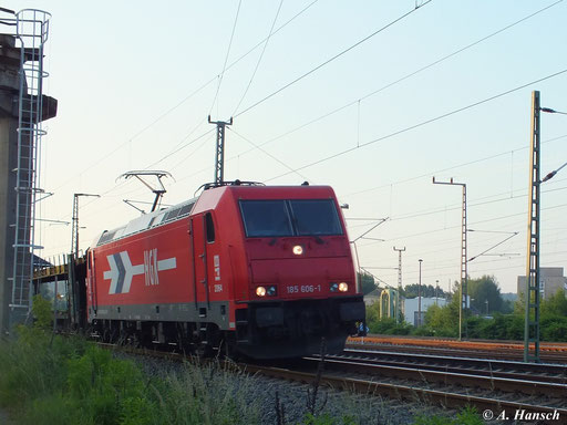 185 606-1 (Lok 2064 der Häfen und Güterverkehr Köln AG) hat am 19. Juni 2013 einen Autoleerzug am Haken, den sie hier am AW Chemnitz vorbei in Richtung Zwickau zieht