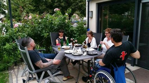 beinamputiert-was-geht e.V. Mitglieder sitzen im Garten am Tisch.