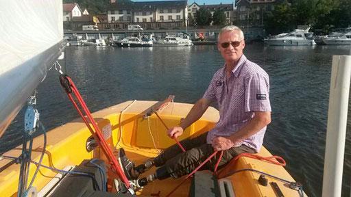 Mann mit zwei Prothesen im Segelboot