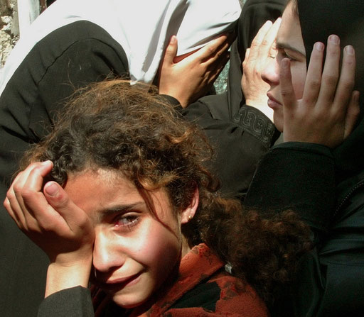 The sister of four-year-old Palestinian girl Elham al-Assar and other relatives cry inside their home at the Nuseirat refugee camp in the central Gaza Strip during her funeral on March, 2003