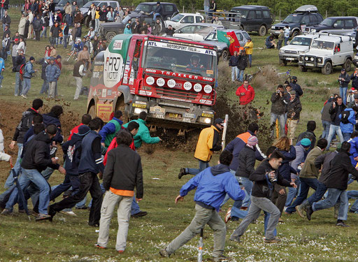 Spectators run away from Spain's driver Fernando Vila Roca sliding his Iveco at Almodovar on Southern Portugal during the 1st stage of the Lisbon-Dakar rally December 31, 2005.