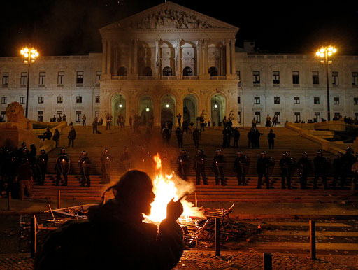 Man protests in front of the Parliament with a fire burning against new 2013 state budget in Lisbon October 15, 2012