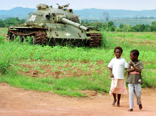 Kids walk past a abbandoned armoured car in Angola on November 1995