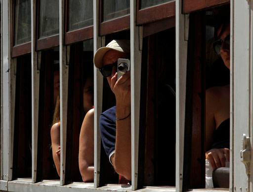 Man takes a photo from the window of tramway in Lisbon old downtown July 8, 2013.