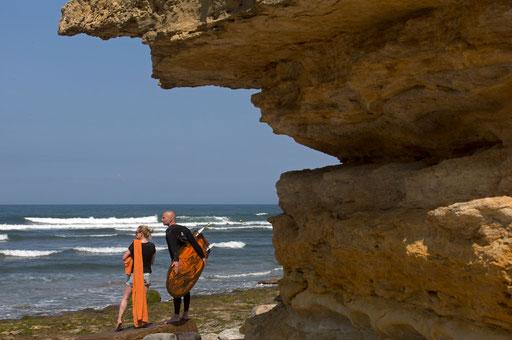 Surfer talks with woman at Ribeira de Ilhas beach July 24, 2014.