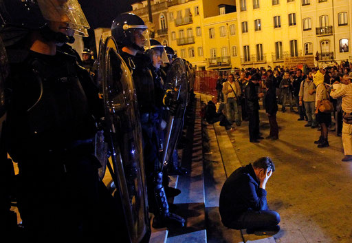 Man seated in the Parliament steps in front of the riot policemen protests against new 2013 state budget in Lisbon October 15, 2012.