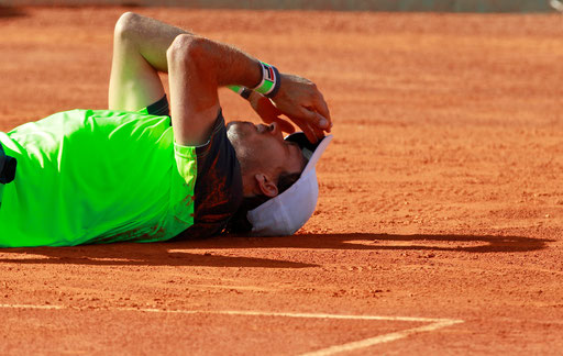 Argentinian tennis player Carlos Berlocq lies on the pitch celebrating his victory after beating Czech Republic Tomas Berdych on the Portugal Open final tennis match at Jamor stadium in Oeiras, outskirts of Lisbon, on May 4, 2014