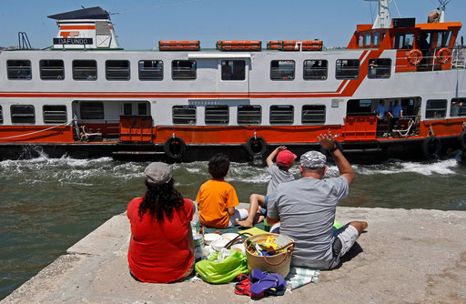 Family having a picnic on the Tagus river side salutes a ferry passengers while waiting to see the Tall Ships Races parade, July 22, 2012.