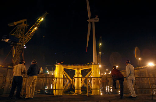 Shipyard workers look at the windmill, Wind Float I, before it is launched to sea in Setubal, 50 km (31 miles) south of Lisbon, September 30, 2011.