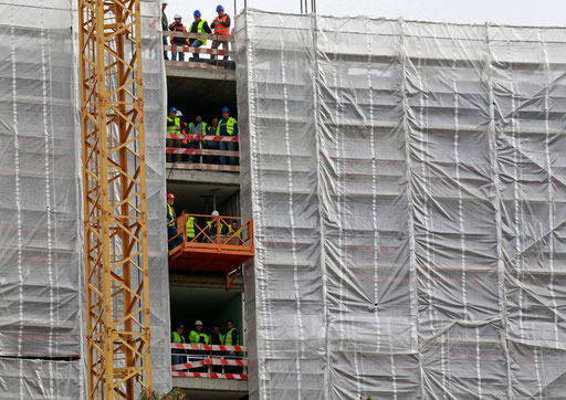 Construction workers pause to watch an event at a Lisbon street on January 2014.