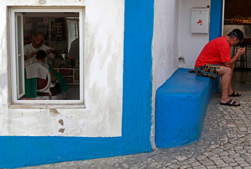 Man rests while beside barber works on his shop in Eiriceira village August 17, 2011.