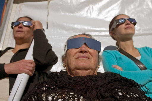 Grandmother mother and daughter watch the annular solar eclipse in Arguzelo with diferent artifacts near the Portuguese Northern city of Braganca October 3, 2005.